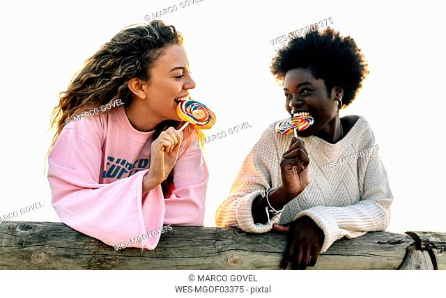 Two best friends eating lollipops outdoors
