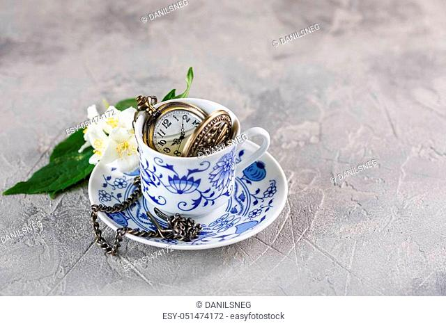 A refined cup of green tea with jasmine and a beautiful clock on a chain inside
