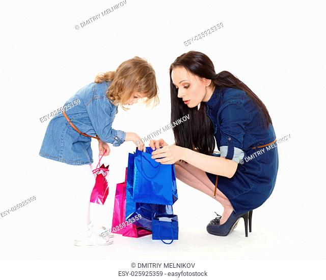 Young beautiful mother and sweet little daughter with shopping bags on a white background. Shopping family