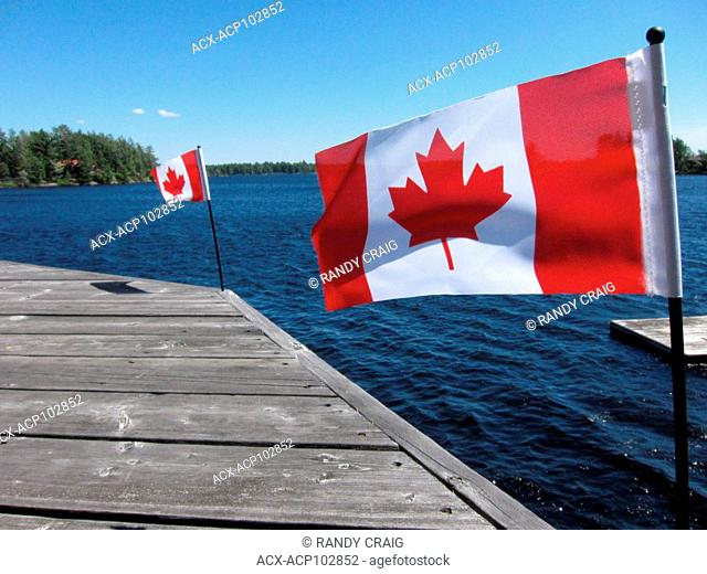 Dock with Canadian flags, Muskoka Country, Ontario, Canada