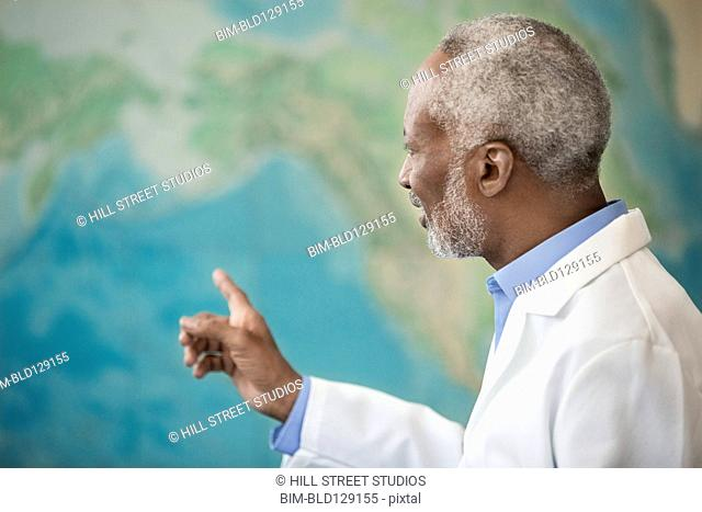 Black doctor examining world map in office