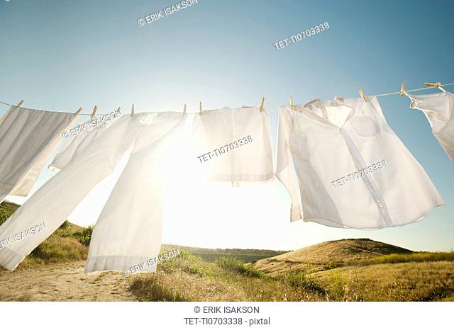 Laundry hanging on clothesline against blue sky