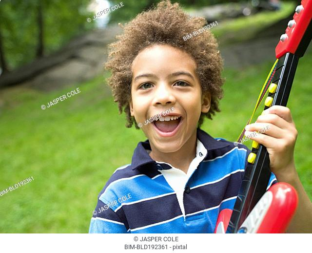 Mixed race boy with plastic guitar