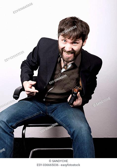 jolly bearded man in a jacket and jeans, sitting on a chair and holding a gun. gangster concept. Negotiations went not on the script, Dangerous Liaisons