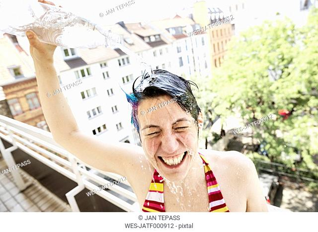 Portrait of laughing woman on balcony showering herself with water