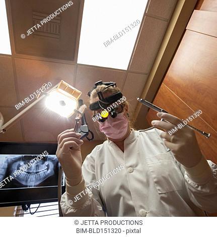 Close up of Caucasian dentist holding tools