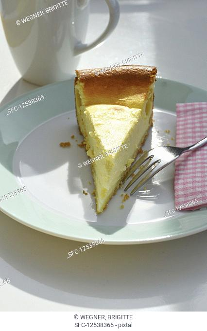 A slice of cheesecake on a plate with a fork