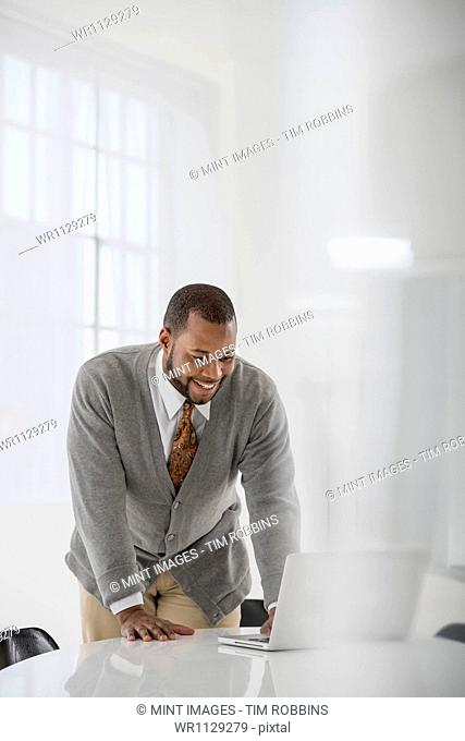A fresh white building interior, flooded with light. A man in a business suit at a table. Using a laptop