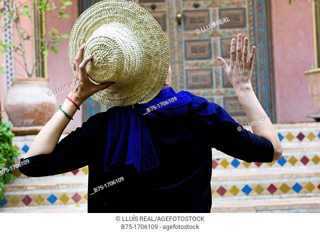 joven de espaldas con sombrero en la mano saludando, Young back with hat in hand saluting