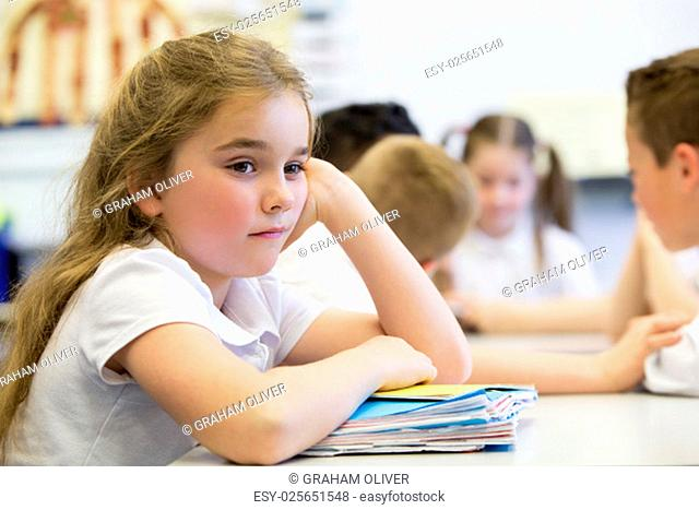 A close up shot of a little girl at school who looks distant and upset
