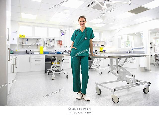 Nurse by table in examination room of vet surgery smiling at camera