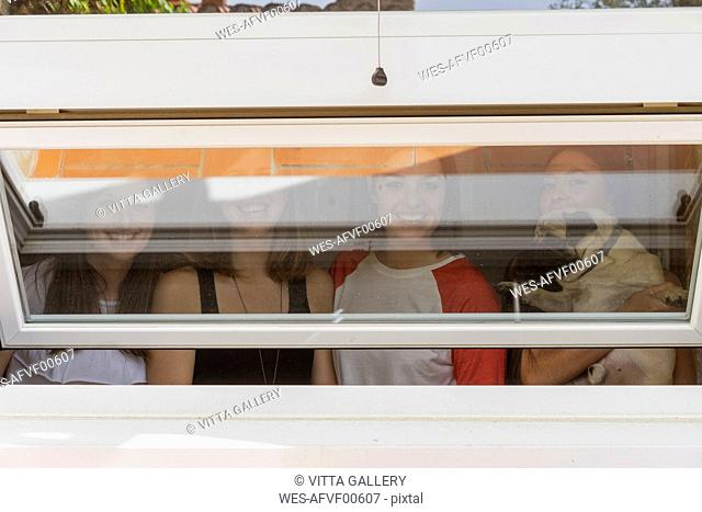 Group picture of four friends with pug behind open hopper window