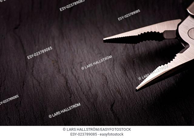Black stone background and steel pliers. Backdrop for work tools, diy and home improvement