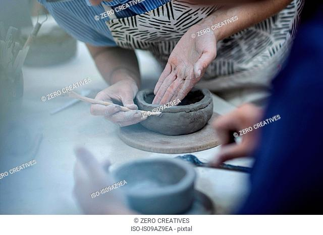 Hands of female potters shaping clay pots in workshop