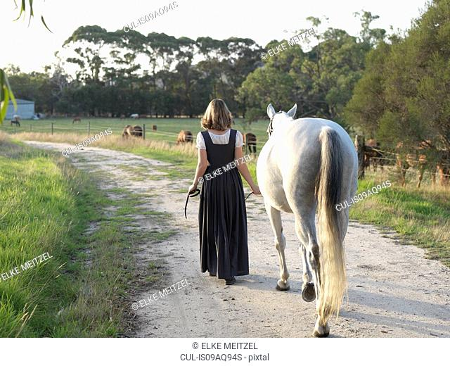 Rear view of teenage girl leading grey horse
