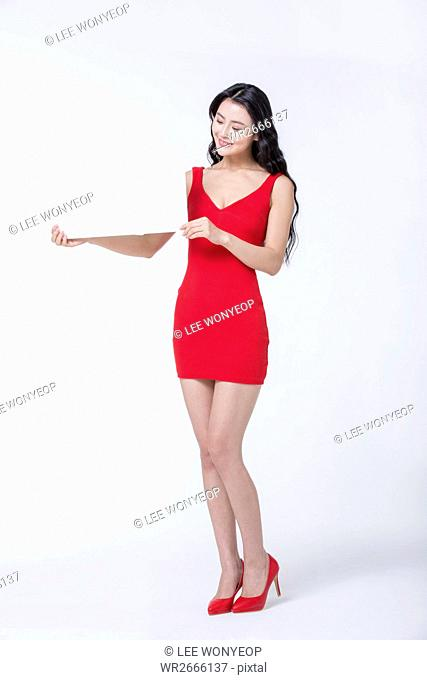 Young smiling slim woman in red dress showing a board