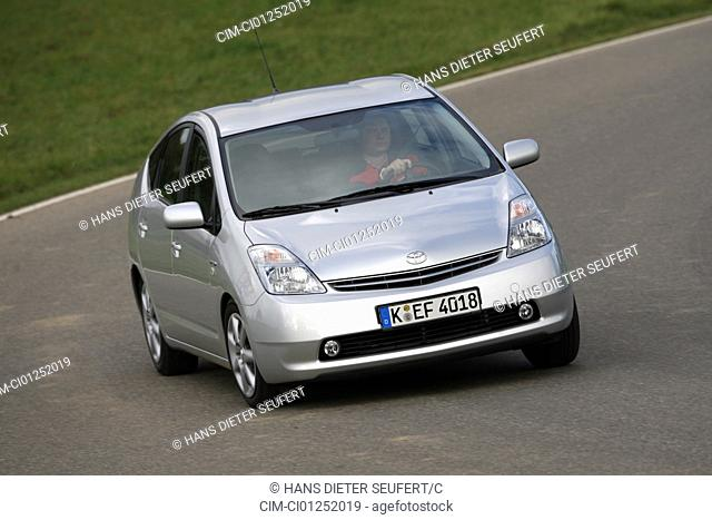 Toyota Prius 1.5 HSD, model year 2006-, silver, driving, diagonal from the front, frontal view, country road, Hybridauto