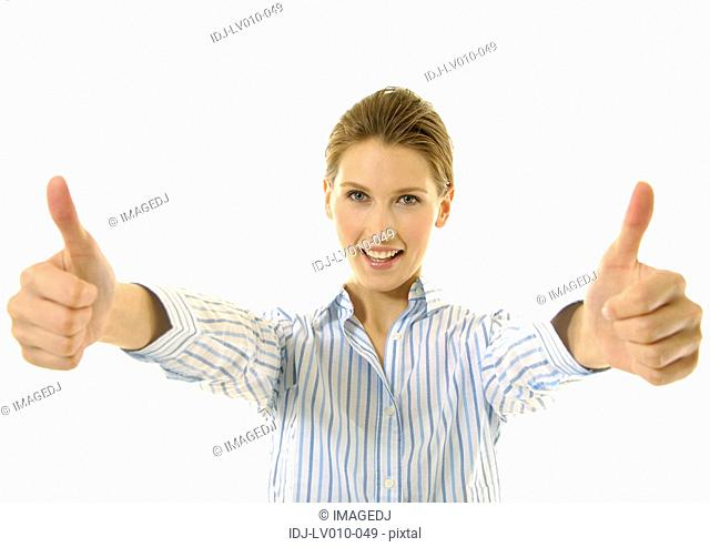 Portrait of a young woman making a thumbs up sign