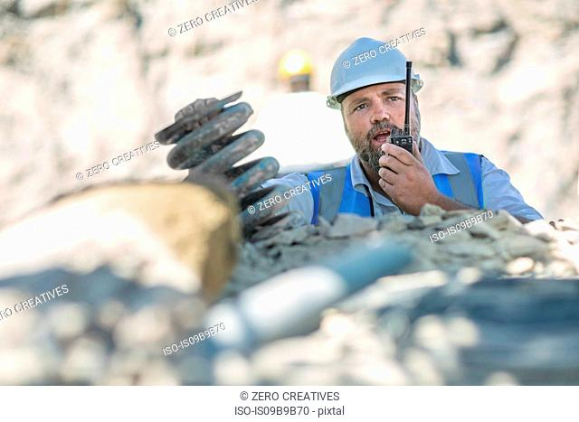Quarry worker in quarry, talking on walkie talkie