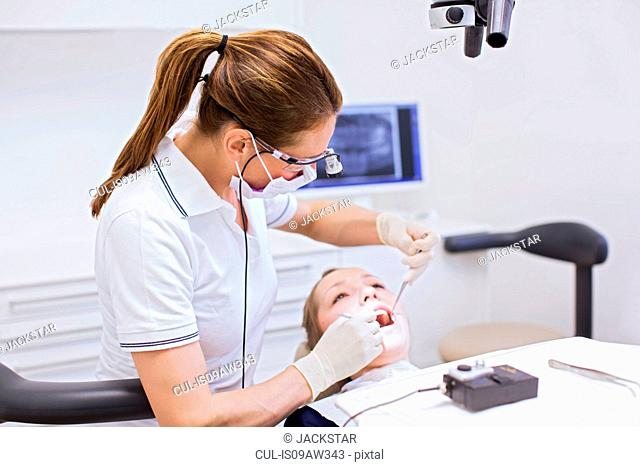Dentist in dental clinic conducting dental examination on young woman
