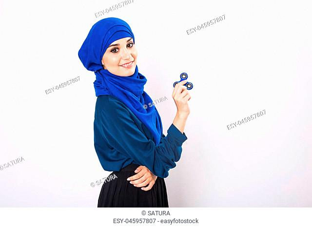 Young beautiful muslim girl holding and playing with fidget spinner. studio shot on white background
