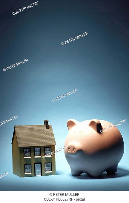 Model house next to piggy bank
