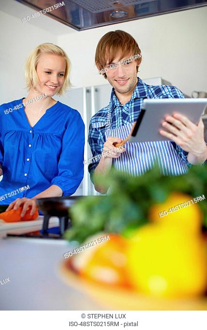 Couple cooking with tablet computer