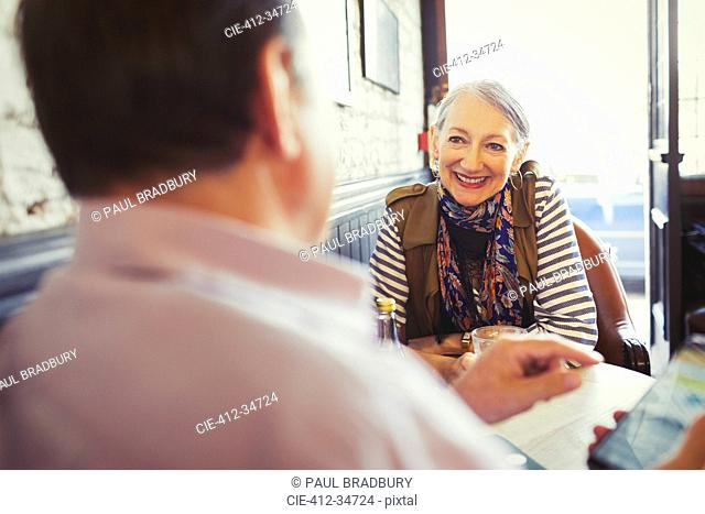 Senior couple talking and using smart phone in cafe