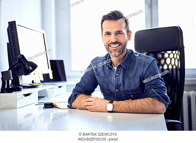 Portrait of smiling man sitting at desk in office