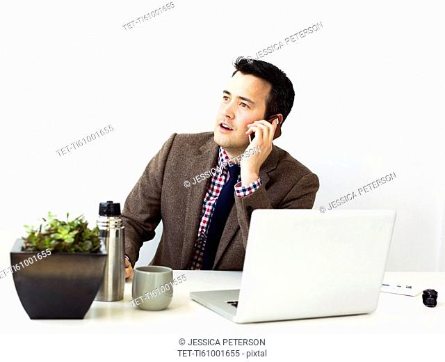 Businessman sitting in office and making phone call