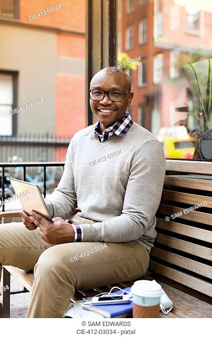 Man using tablet computer on city street