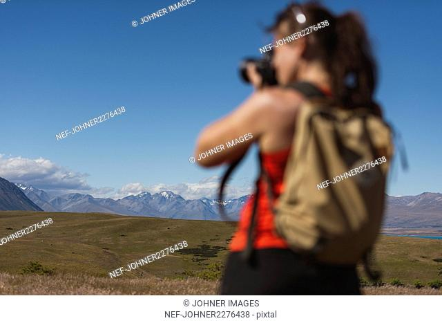 Young woman photographing mountains