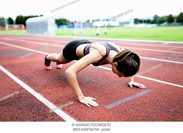 Teenage runner doing push ups on race track