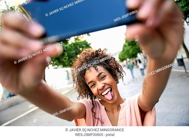 Carefree young woman taking a selfie in the city