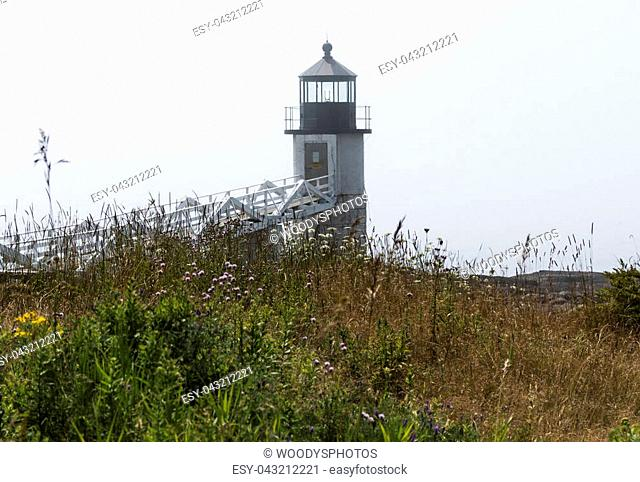 The Marshall Point Lighthouse in Maine with fog over the water and tall grass, plants and fowers in view as the fog burns off