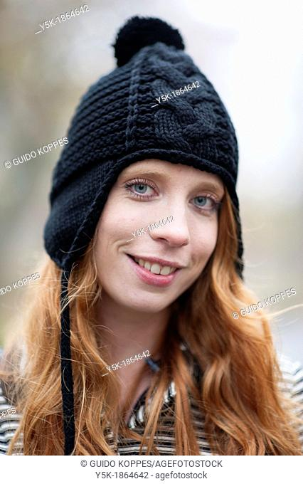 Breda, Netherlands. Young, fashionable and redheaded woman in a city-park