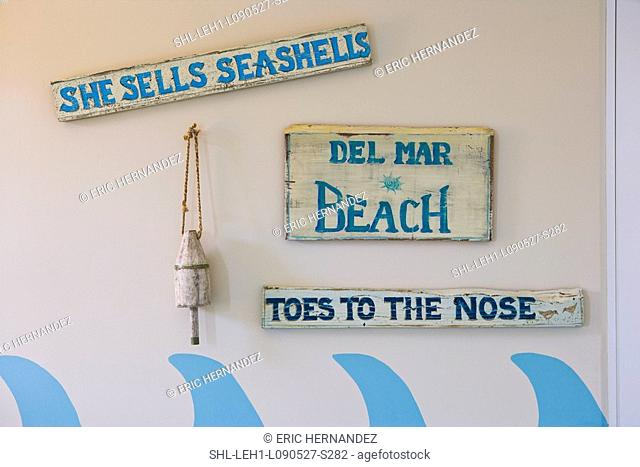 Decorative beach signs hanging on wall