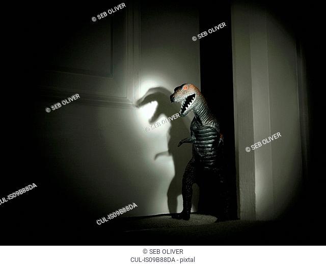 Toy dinosaur spotlit in darkened doorway