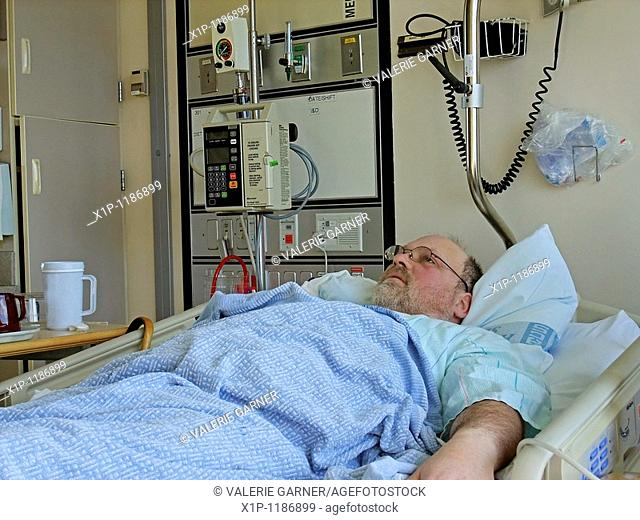 This image is a middle aged bearded Caucasian man who's lying in a hospital bed in the hospital with a tray beside the bed and other medical objects