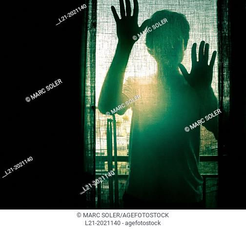 Silhouette of a man and his hands behind a window
