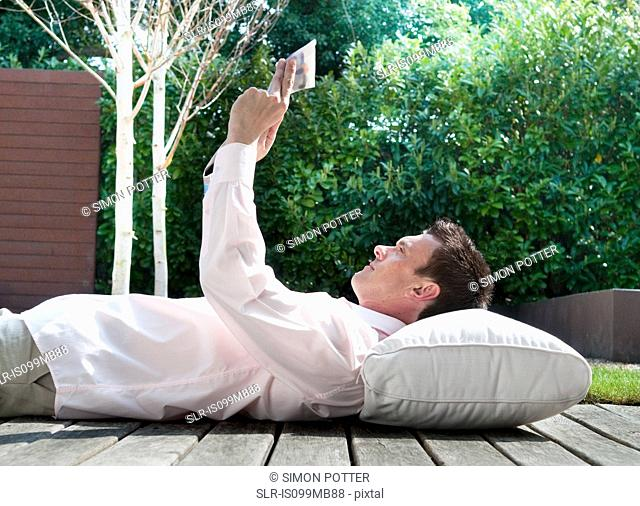 Businessman lying on decking reading newspaper