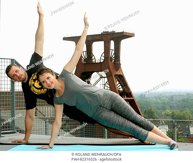 Siblings Madita and Frederik Reimann practice a yoga position on the roof of the Zollverein Coal Mine Industrial Complex in Essen, Germany, 27 July 2016