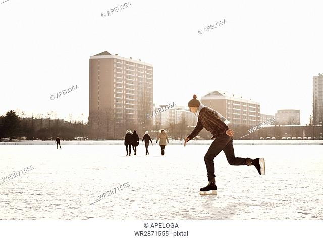 Side view of man skating on ice rink at park in city