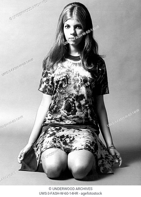 United States: 1969 A young woman kneeling and wearing a tie-dyed shirt with a tie-dyed scarf draped across her legs