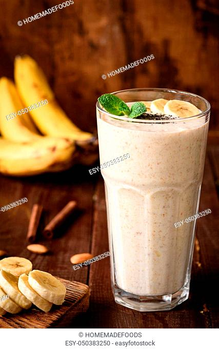 Banana smoothie in tall glass on wooden background. Healthy nutritious vegan drink, power boost, fitness, dieting food. Concept of healthy eating, dieting