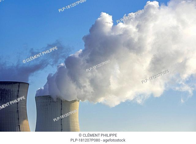 Two cooling towers of nuclear power station / nuclear power plant and massive cloud of water vapour / steam against blue sky