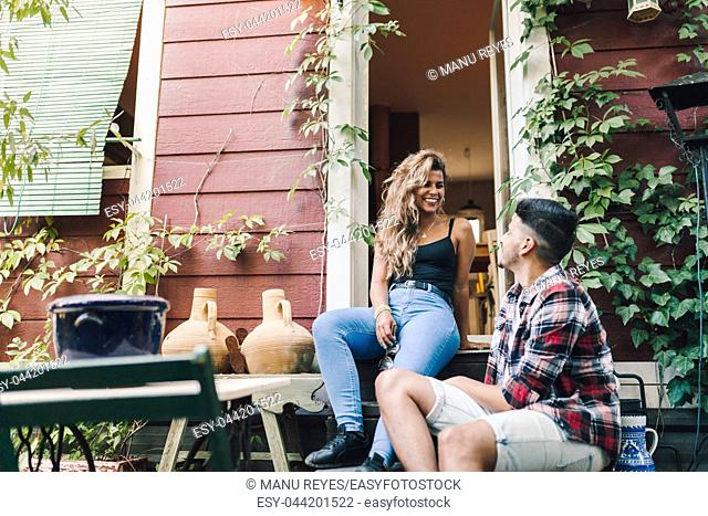 Young couple smiling sitting on the steps outside the wooden cabin