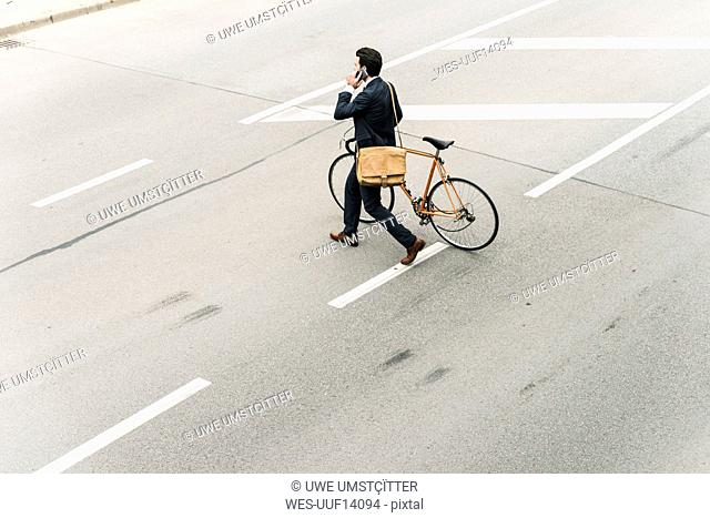 Businessman with bicycle on cell phone walking on the street
