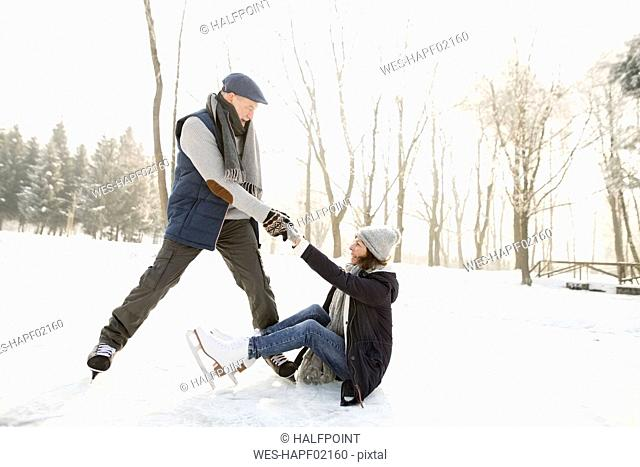 Man helping ice skating woman getting up from frozen lake