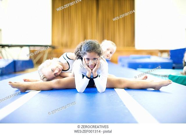 Three girls doing gymnastics exercise on floor